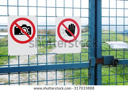 Signs on iron fence with a door lock