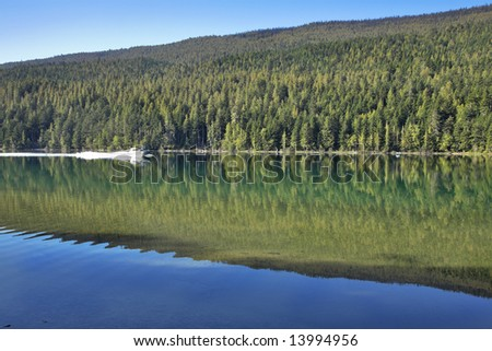 Silent fishing lake and a prompt boat - stock photo