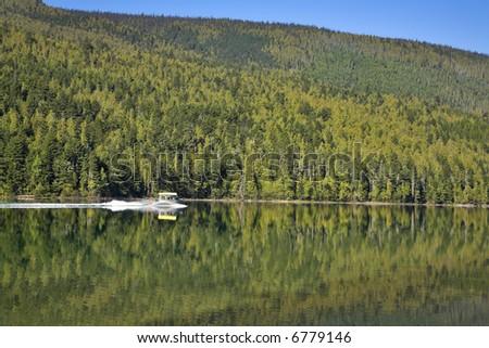 Silent fishing lake and a rash boat - stock photo