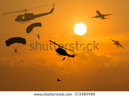 silhouette airplane,helicopter  and  parachute at sunset. - stock photo