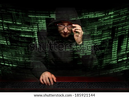Silhouette hacker in futuristic environment hacking information on tech background with binary codes and words - stock photo