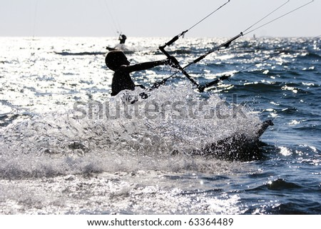 silhouette of a kitesurfer jumping in the waves - stock photo