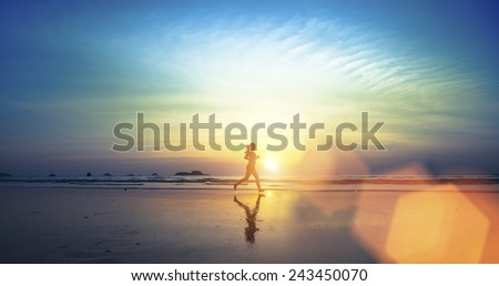 Silhouette of a young girl running along the beach of the sea during an amazing sunset. - stock photo