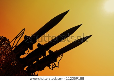 Silhouette of antiaircraft defense rockets . Shadows of the war. - stock photo
