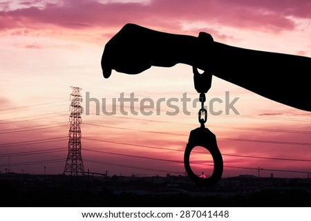 silhouette of hand women in shackle on city sunset background - stock photo