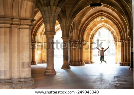 Silhouette of happy girl jumping high up in cloisters of Glasgow University. Scotland. Summertime outdoors. - stock photo