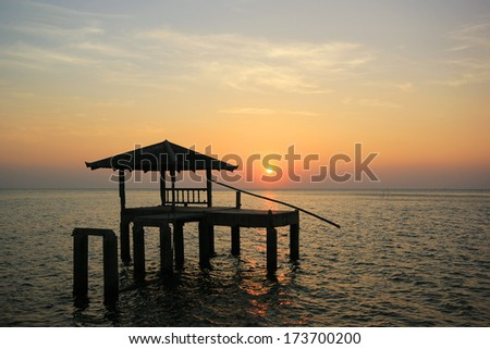 Silhouette of old pavilion in the sea at sunset