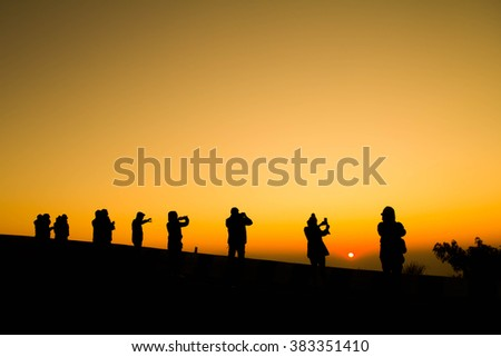 Silhouette of travelers enjoy their moment watching and take picture sunset