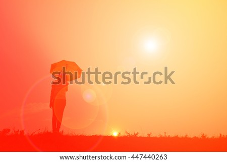 Silhouette women with umbrella at sunset