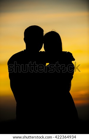 Silhouettes of couple against the sunset sky. - stock photo