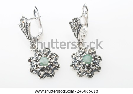 Silver earrings with emerald gemstone isolated on white background - stock photo