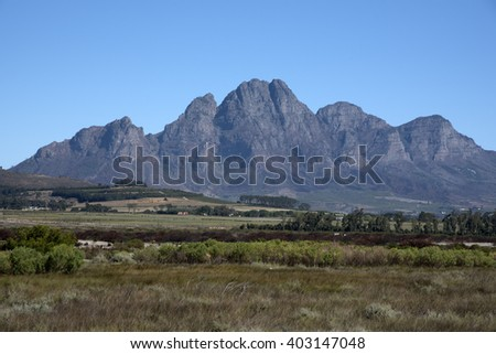 SIMONSBERG MOUNTAIN STELLENBOSH SOUTH AFRICA - APRIL 2016 - The Simonsberg Mountain seen across open farmland close to Stellenbosch in the Western Cape South Africa - stock photo