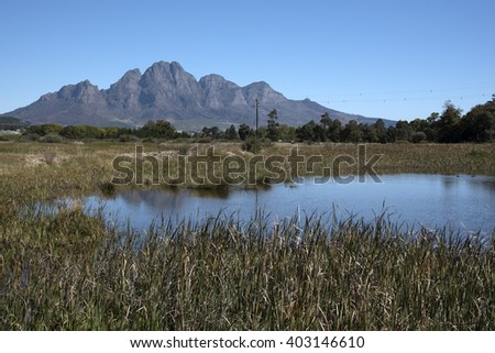 SIMONSBERG MOUNTAIN STELLENBOSH SOUTH AFRICA - APRIL 2016 - The Simonsberg Mountain seen across a farm dam close to Stellenbosch in the Western Cape South Africa - stock photo