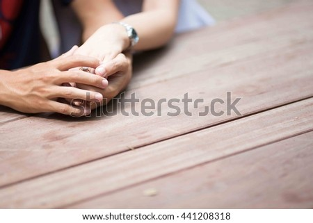 sitting at a wooden table holding hands