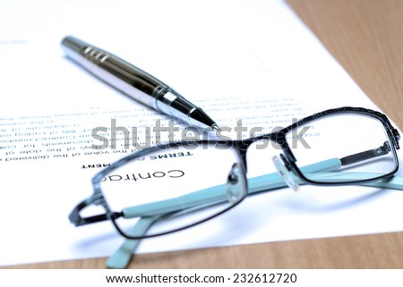 Siver Pen on the contract papers, glasses above - stock photo