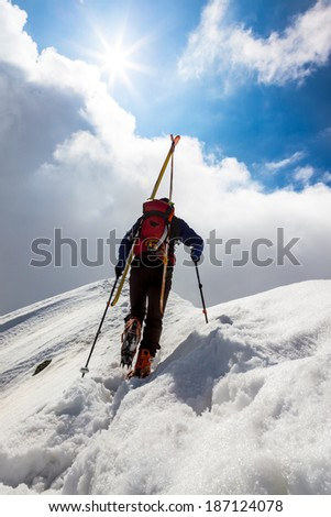 Ski mountaineer walking up along a steep snowy ridge with the skis in the backpack. In background a dramatic sky with a shiny bright sun. Concepts: adventure, achievement, courage, determination. - stock photo