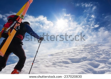 Ski mountaineer walking up along a steep snowy ridge with the skis in the backpack. In background a dramatic sky. Concepts: adventure, achievement, courage, determination, extreme sport - stock photo