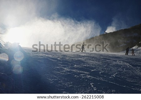 Skier near a snow cannon making fresh powder snow. Snow making on slope. Mountain ski resort and winter calm mountain landscape.   - stock photo