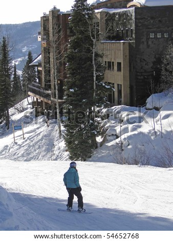 Skiers slide down to the resort base area in Steamboat Springs, Colorado - stock photo