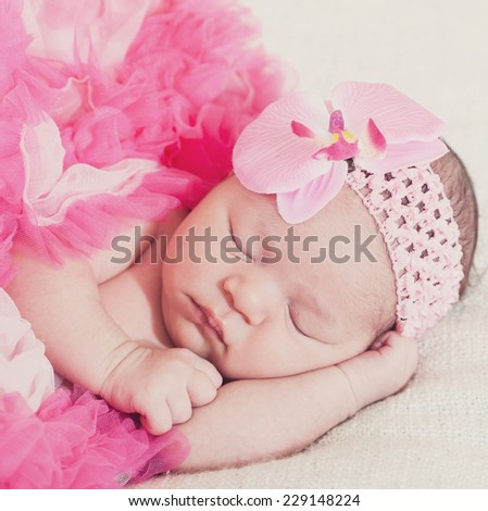 sleeping newborn girl in pink laces  - stock photo