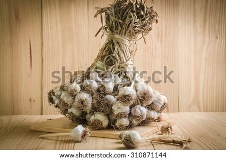 sliced garlic, garlic clove, garlic bulb in wicker basket place on chopping block on vintage wooden background  - stock photo