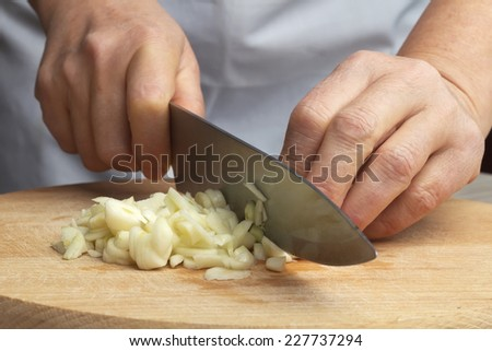 Slicing garlic cloves on the cutting board with a knife - stock photo