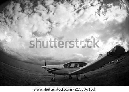 small airplane on green grass and sunset background  - stock photo