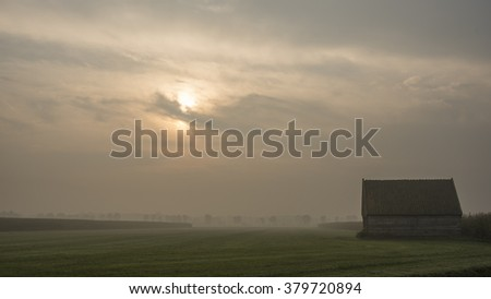 Small barn on a foggy morning at sunrise with grassland - oude vervallen schuur - stock photo