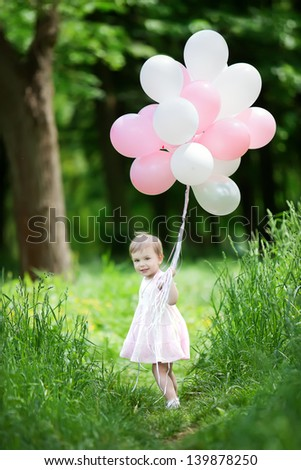Small caucasian plays in summer park with colorful baloons - stock photo