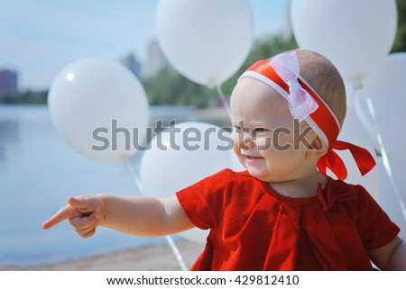 Small caucasian plays on river bank with white balloons. Portrait of cute adorable baby girl in red dress celebrating her first birthday on sunny sand beach with balloons looking away from camera - stock photo