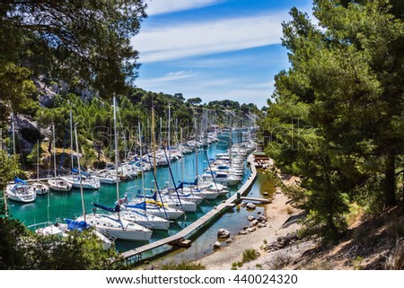 Small fjords in Calanque National Park between Marseille and Cassis.  White sailboats moored in rows near the shore - stock photo