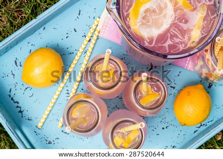 4 small glass bottles and pitcher filled with fresh squeezed pink lemonade with yellow swirled straws and lemon slices sitting on weather blue drink tray from above - stock photo