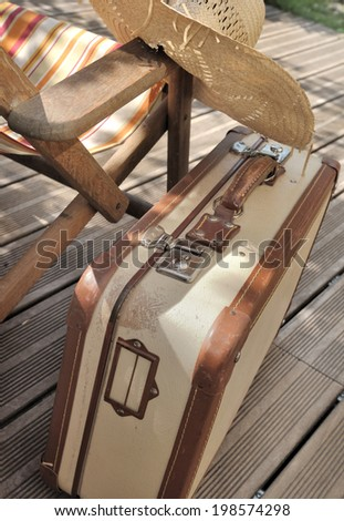 small retro suitcase next to a lounge chair on wooden terrace