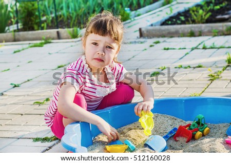 small, sad girl, playing in a sandbox in the yard on a summer day