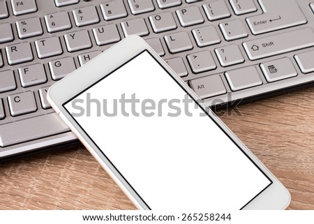 Smartphone laying on  keyboard with copy space on screen - stock photo