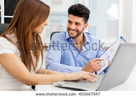 Smiling business people using a laptop computer in their office