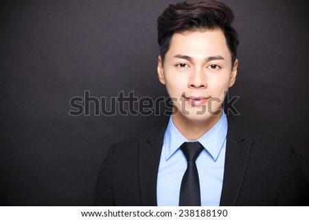 Smiling businessman standing before black background - stock photo