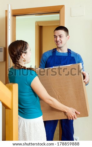 Smiling delivary person in uniform delivered a parcel to woman at home