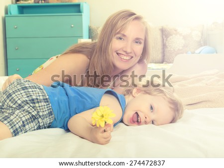 Smiling embracing mom with her baby lying in bed