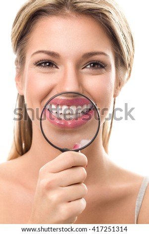Smiling girl with perfect teeth behind magnifying glass - stock photo