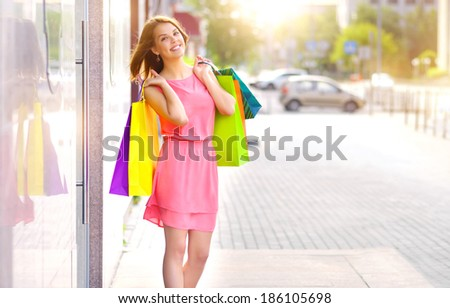Smiling girl with shopping bags. Background windows - stock photo