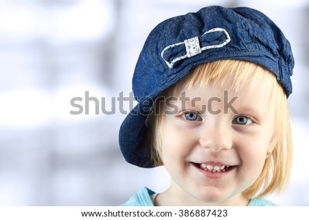smiling little girl   with a cap on her head on a blue  background