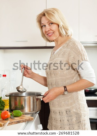 Smiling mature  woman  with ladle cooking soup in pan  in kitchen  home  interior