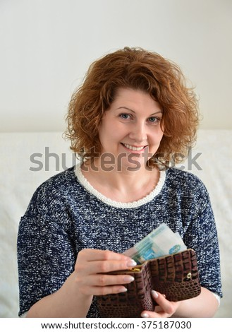 smiling middle-aged woman pulls money out of purse - stock photo