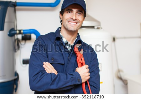 Smiling technician repairing an hot-water heater  - stock photo