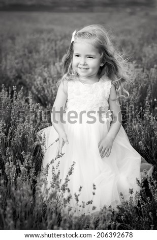 Smiling toddler girl in lavender field ( black and white ) - stock photo