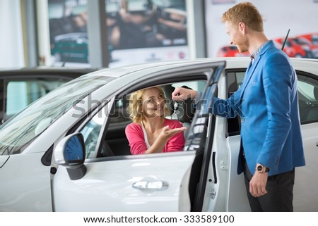smiling woman receives the keys to a new car from a sales manager - stock photo