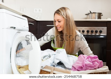 Smiling  woman working near washing machine  at home