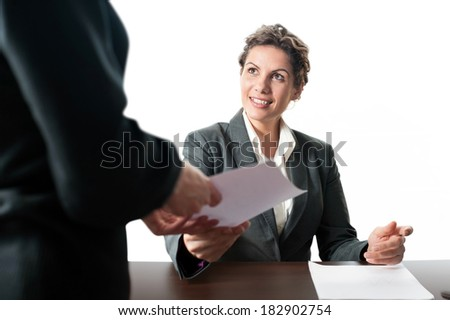 Smiling young businesswoman sitting at desk receiving a contract from a office worker - stock photo