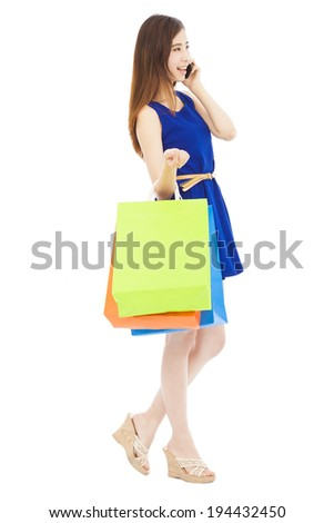 smiling young  woman holding shopping bags and talking on the phone - stock photo
